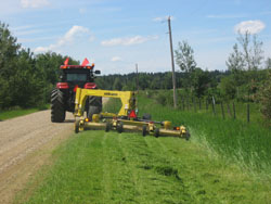 A large mower pulled by a tractor along the side of a road