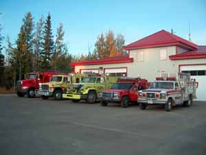 Five fire rescue vehicles parked in front of a fire department facility