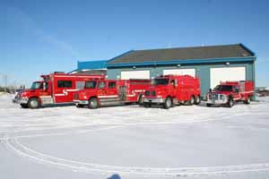 Four fire rescue vehicles parked outside of a fire station